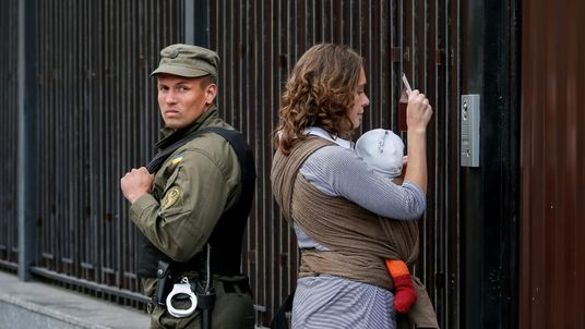 A woman shows her passport to enter the Russian embassy and take part in the Russian parliamentary election as a member of the National Guard stands guard in Kiev, Ukraine