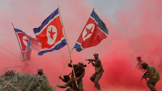 South Korean soldiers wear North Korea's military uniforms and hold North Korea's flags, acting as North Korean soldiers, as they take part in a re-enactment the battle of the Korean war during a commemorative war victory event to mark the 66th anniversary