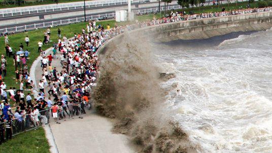 People run away from waves as they watch tidal bore in Hangzhou, Zhejiang Province, China