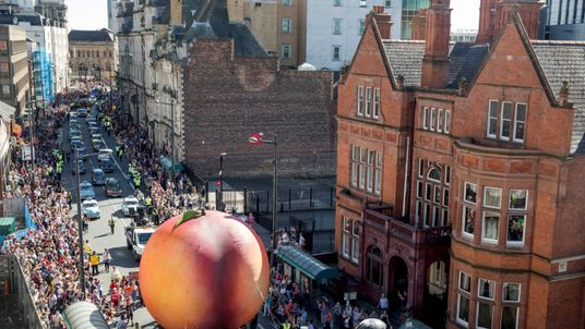 Members of the public gather to watch a giant peach as it is moved through the centre of Cardiff as part of a street performance to mark the start of City of the Unexpected, a celebration of the author Roald Dahl