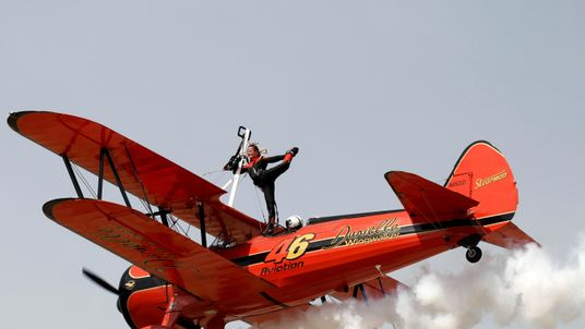 Danielle Hughes performs on a plane piloted by Emilliano Del Buono during the Athens Flying Week aviation event over the Tanagra air base in northern Athens, Greece