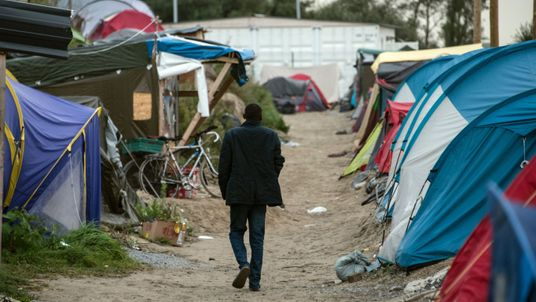 TOPSHOT - A migrant walks on September 26, 2016 in the so-called 'Jungle' migrant camp in the French northern port city of Calais. French President Francois Hollande said on a visit to the port of Calais on September 26, 2016 that the sprawling 'Jungle' migrant camp would be 'definitively dismantled' under a plan to relocate the migrants to centres around the country. Hollande, on his first visit to Calais as president, also called on British authorities to 'play their part' in assisting the mig