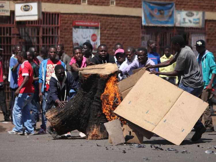 Opposition supporters burn wood and cartons as they clash with police