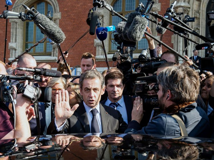 Former French president and candidate for the right-wing Les Republicains (LR) party primary ahead of the 2017 presidential election Nicolas Sarkozy (C) surrounded by journalists, gestures as he leaves Calais' townhall, northern France, on September 21, 2016 with Calais Mayor Natacha Bouchart (L) after delivering a speech during a visit. Seven candidates including ex-president Nicolas Sarkozy were confirmed on September 21 to contest the rightwing primary to pick a nominee for France's president
