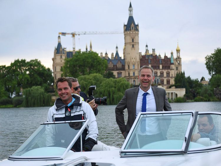 AfD candidate Leif-Erik Holm waves from a boat after exit polls suggest they beat Angela Merkel's party
