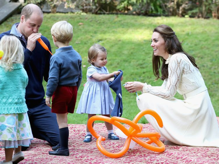 William blows up a balloon for George as Kate watches on