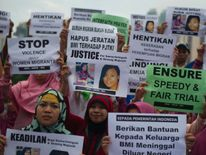 Indonesian migrant workers hold up placards of slain colleagues Seneng Mujiasih and Sumarti Ningsih