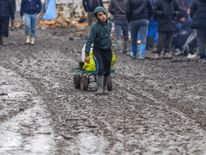 A young migrant pulls a trolley in a muddy field at a camp of makeshift shelters for migrants and asylum-seekers from Iraq, Kurdistan, Iran and Syria, called the Grande Synthe jungle, near Calais, France, February 3, 2016. European Union countries on Wednesday approved a 3 billion euro ($3.32 billion) fund for Turkey to improve living conditions for refugees there in exchange for Ankara ensuring fewer of them migrate on to Europe. REUTERS/Yves Herman