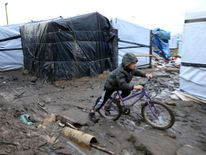 "A young boy from Afghanistan pushes his bycicle in the mud in the southern part of the camp known as the ""Jungle"", a squalid sprawling camp in Calais, northern France, February 25, 2016. A French judge on Thursday upheld a government plan to partially demolish a shanty town for migrants trying to reach Britain on the outskirts of the northern port of Calais, an official spokesman said. REUTERS/Pascal Rossignol"