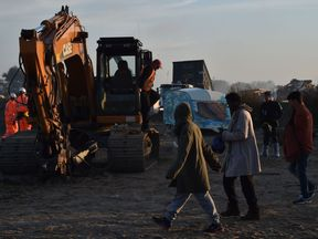 Migrants walk past excavators being used by a demolition crew