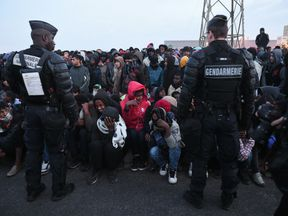 French anti-riot police stand guard as migrants queue to leave the camp