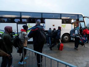 Migrants carry their belongings as they board a bus