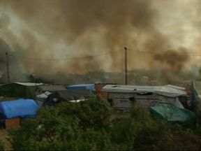 Fire spreads through 'The Jungle' as authorities try to clear the site