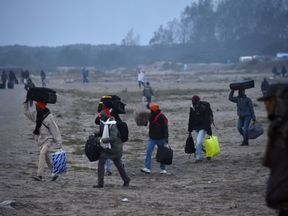 Migrants carry their luggage as they walk towards official meeting points set by French authorities as part of the full evacuation of the Calais 'Jungle' camp