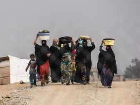 Iraqi families displaced by fighting around Mosul walk at a camp near Qayyarah