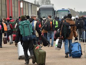 Migrants carrying their luggage embark buses to leave the 'Jungle'