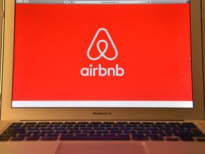 The Airbnb logo is displayed on a computer screen