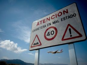 A plane flies near a sign on the edge of Malaga Airport. File picture