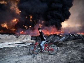 A boy pauses on his bike as he passes an oil field in Qayyarah, Iraq, that was set on fire by retreating ISIS fighters ahead of the Mosul offensive