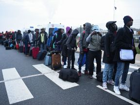 Migrants queue at official meeting points set by French authorities