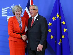 The PM, pictured with Jean-Claude Juncker, admits there may be  'difficult moments' ahead