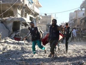 An injured person is carried on a stretcher after an airstrike in a rebel-held area of Aleppo on Friday