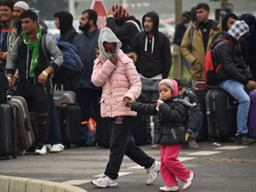 A migrant with her child walks past others waiting to be transferred from the camp