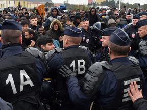 French riot police officers hold back migrants