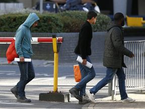 Two members of a group of unaccompanied minors (L and 2nd L) from the Jungle migrant camp in Calais walk outside an immigration centre after being processed after their arrival in Britain, in Croydon,