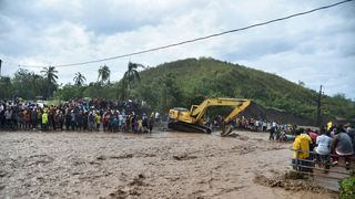 Haitians wait to cross the river La Digue in Petit Goave where the bridge collapsed