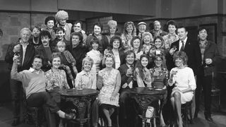 The cast of the Coronation Street celebrate the programme's Silver Jubilee on the set in Manchester in 1985. Jean Alexander as Hilda Ogden sits in the centre at the front