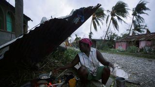 A woman cooks next to a house damaged by Hurricane Matthew in Les Cayes, Haiti
