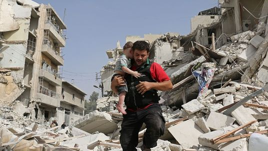 A Syrian man carries a baby after removing him from rubble in Aleppo
