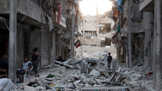 Residents inspect a damaged site after an airstrike in the besieged rebel-held al Qaterji neighbourhood of Aleppo,