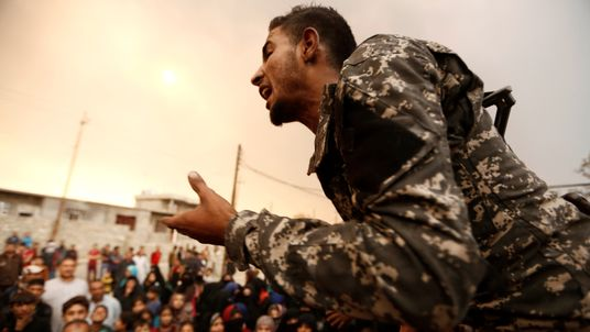 An Iraqi soldier tries to calm displaced people who are complaining about the lack of food supplies outside a processing centre as smoke from burning oil refinery blanketed Qayyara, south of Mosul