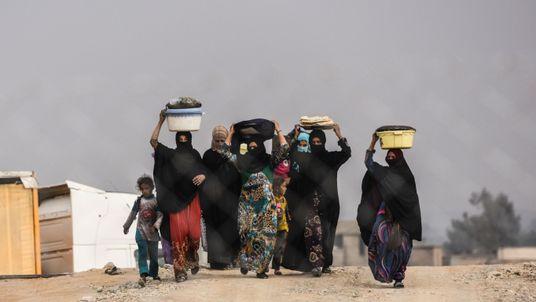 Iraqi families displaced by fighting around Mosul walk at a camp near Qayyarah