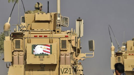 Members of Iraqi forces look at a MRAP armoured vehicle used by US forces supporting Iraq troops