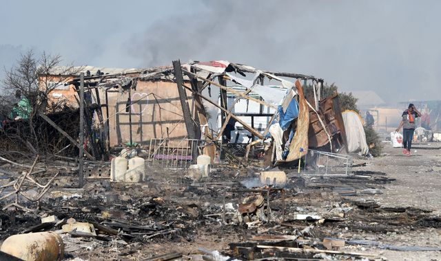 Migrants sleep in the charred remains of the 'Jungle' camp in Calais