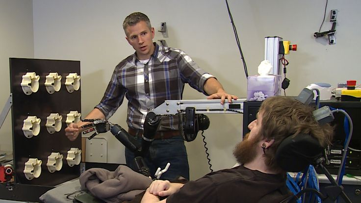 Paralysed Nathan Copeland experiences feeling in his fingers thanks to robotic arm. Pictured with researcher Robert Gaunt.