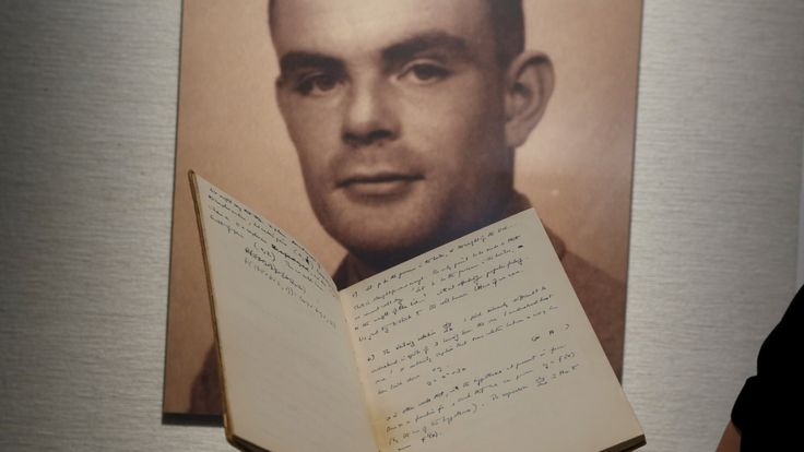 A notebook of British mathematician and pioneer in computer science Alan Turing is displayed in front of a photo of him during an auction preview in Hong Kong March 19, 2015. The notebook about mathematics and computer science written by Nazi-code breaker Turing will be sold at an auction, Bonhams auction house said in January. The 56-page manuscript is expected to fetch at least seven figures, with a portion of the proceeds going to charity, when it goes up for sale on April 13 in New York. REU