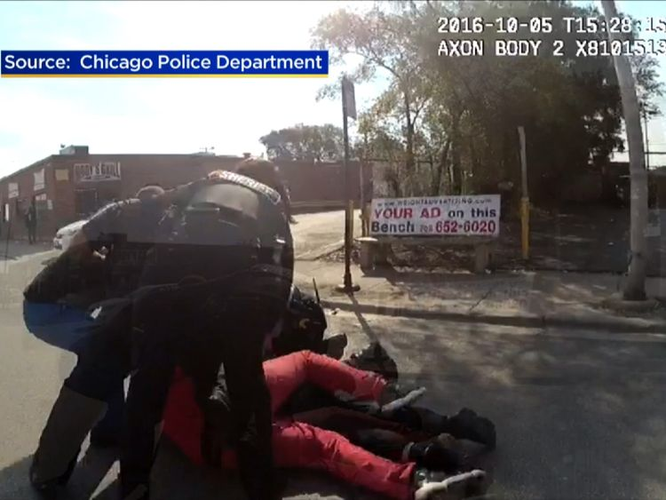 Chicago police try to restrain a man attacking a female colleague.