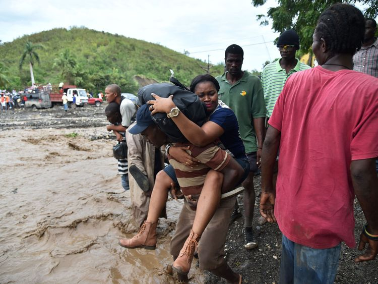 haitian people cross the river La Digue in Petit Goave where the bridge collapsed during the rains from Hurricane Matthew, southwest of Port-au-Prince, October 6, 2016. Hurricane Matthew has left at least 23 people dead in Haiti, a toll likely to climb as authorities re-establish contact with the hardest-hit areas where the damage is 'catastrophic,' officials said. The Caribbean's worst storm in nearly a decade, Matthew slammed into Haiti, the Americas' poorest nation, with heavy rains and devas