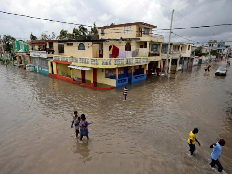 People walk in a flooded area after Hurricane Matthew in Les Cayes, Haiti