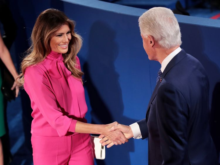 Melania Trump shakes hands with former US President Bill Clinton before the town hall debate at Washington University on October 9, 2016