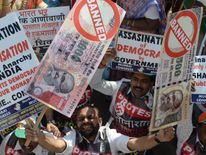 An Indian protestor holds placards of banned 500 and 1000 rupee notes during a protest against demonetisation, in Mumbai on November 28, 2016. Tens of thousands of people turned out November 28, for nationwide protests against India's controversial ban on high-value banknotes, which opposition party organisers say has caused a 'financial emergency