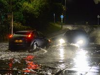 Cars drive through flash flooding in Plympton, Devon. /p pPic: Matt Gilley
