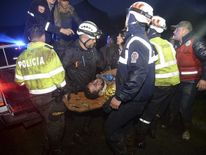 Rescuers carry one of the survivors