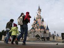Visitors walk towards the Sleeping Beauty Castle at Disneyland Paris