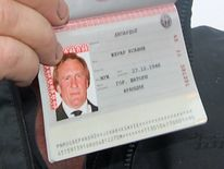 A close up of French actor Gerard Depardieu, who has threatened to quit his homeland to avoid higher taxes, showing off his new Russian passport on January 6, 2013 at Mordovia airport in Saransk where he has been offered residence in this central Russia region known for Stalin-era Gulag labour camps. The former Oscar nominee travelled to snow-covered Mordovia a day after he met with strongman President Vladimir Putin at his sumptuous Black Sea villa in the resort town of Sochi for friendly bante
