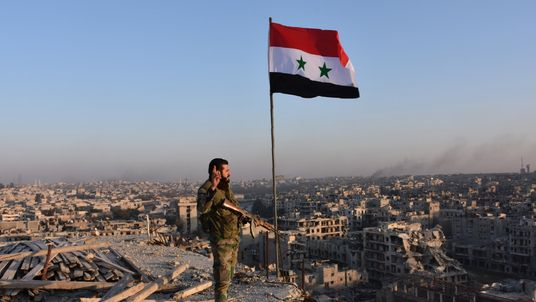 A pro-government fighter overlooks Aleppo in the city's Bustan al Basha neighbourhood
